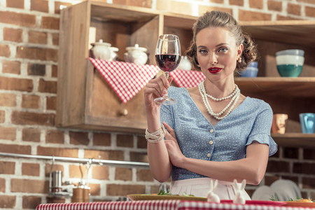 beautiful adult housewife with glass of red wine looking at camera at kitchen Stok Fotoğraf