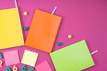 flat lay with colorful notebooks and appliances on pink Imagens