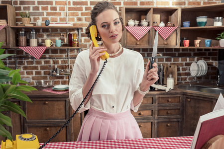 serious adult housewife with knife talking by yellow wired phone at kitchen Stock Photo