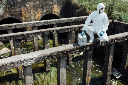 male scientist in protective mask and suit sitting with working suitcase near sewerage