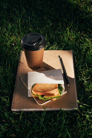 close up view of notebooks, sandwich and coffee to go on green grass Imagens