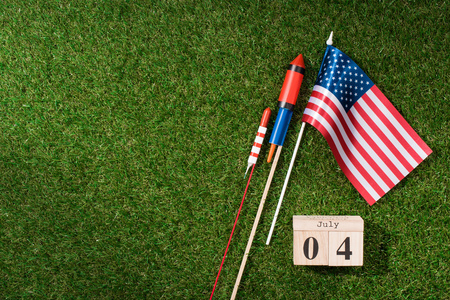 flat lay with american flagpole, wooden calendar with 4th july date and fireworks on green grass, americas independence day concept