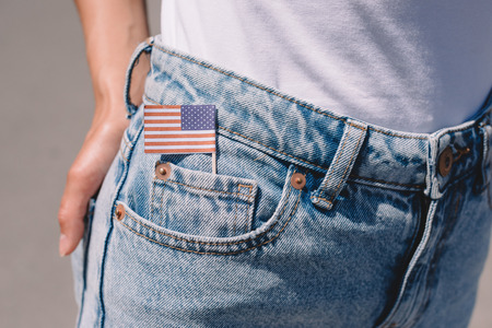 partial view of woman in jeans with american flagpole in pocket, americas independence day holiday concept Banco de Imagens
