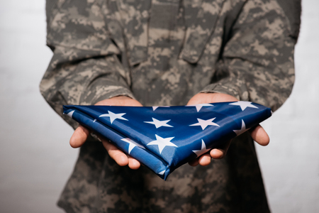 partial view of soldier in military uniform showing folded flag in hands, americas independence day concept 写真素材