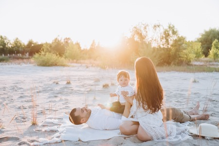 happy family spending time with son on beach with sunlight Stok Fotoğraf
