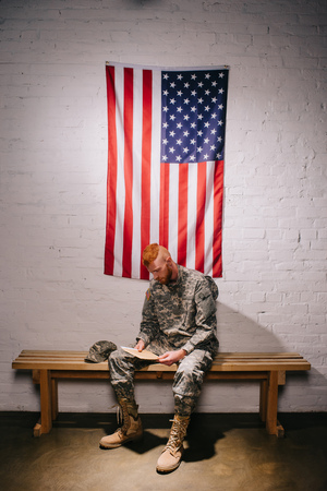 red hair american soldier with letter sitting on wooden bench with flag on white brick wall behind, americas independence day concept 写真素材