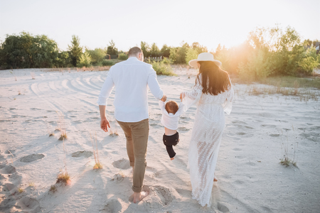 rear view of family holding hands with baby on beach with back light