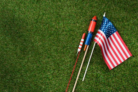 flat lay with american flagpole and fireworks on green grass, americas independence day concept 写真素材