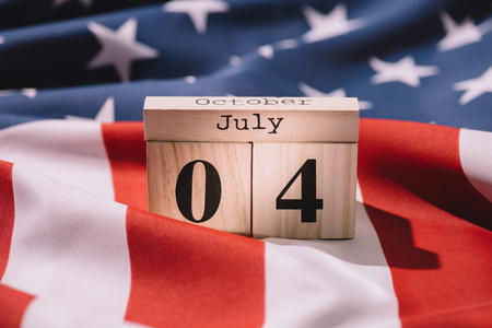 close up view of wooden calendar with 4th july date on american flag, americas independence day concept