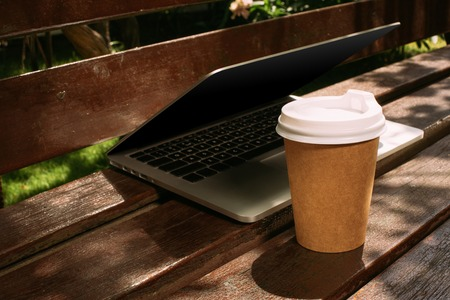 close up view of laptop and coffee to go on wooden bench