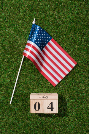 top view of american flagpole and wooden calendar with 4th july date on green grass, americas independence day concept 写真素材