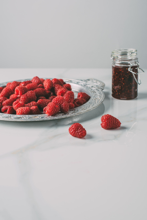 selective focus of silver tray with raspberries and jar of jam on marble table