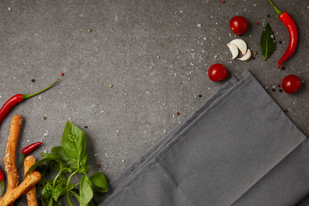 top view of grey napkin with vegetables and bread sticks on grey table Banco de Imagens
