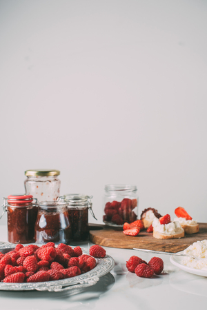 selective focus of raspberries and jars with fruit jam on grey