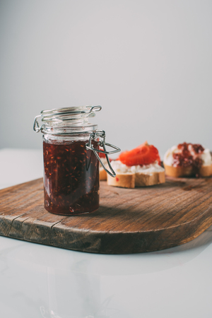 selective focus of jar with fruit jam on cutting board on grey