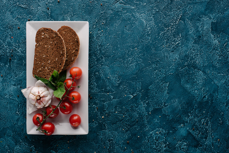 Plate with bread piece and red tomatoes on dark table