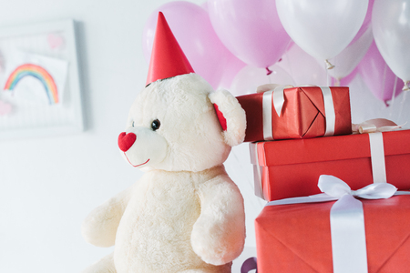 selective focus of teddy bear in cone with gift boxes and air balloons