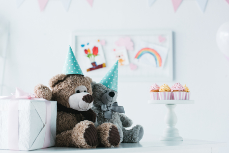 teddy bears in cones on table with cupcakes on stand and present box