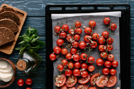 Baked cherry tomatoes with garlic and cheese on dark wooden table with bread and oil Imagens
