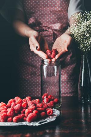 cropped image of woman in apron putting raspberries in jar for making jam Standard-Bild - 105682591