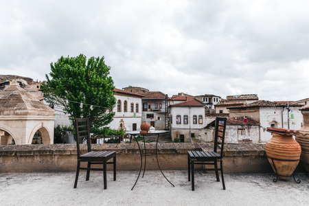 round table and wooden chairs on terrace and historical houses behind in cappadocia, turkey 版權商用圖片