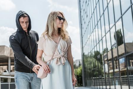 criminal man pickpocketing from womans bag on street Фото со стока