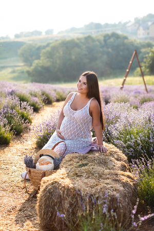 smiling pregnant woman sitting on hay bale in violet lavender field and looking away
