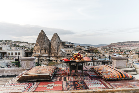 round table, pillows and traditional carpet on terrace and beautiful scenic of buildings and rocks in cappadocia, turkey Imagens