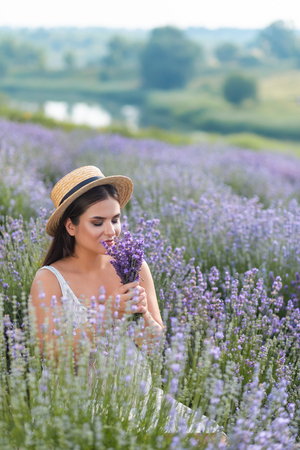 attractive pregnant woman in straw hat sniffing lavender flowers in field