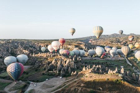 CAPPADOCIA, TURKEY - 09 MAY, 2018: hot air balloons flying above beautiful bizarre rock formations in goreme national park, cappadocia, turkey Imagens