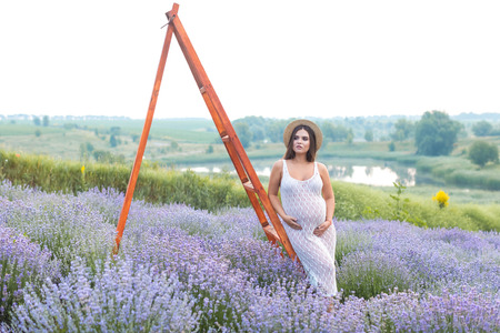 attractive pregnant woman in straw hat leaning on wooden ladder at lavender field and touching belly