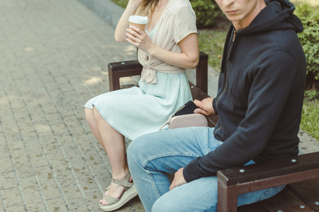 cropped view of man pickpocketing wallet from womans bag on bench in park
