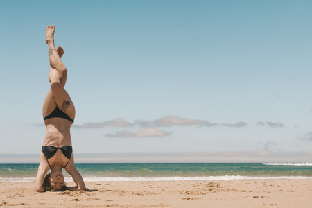 young woman practicing headstand on sandy beach on summer day