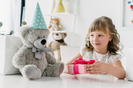 cute little kid giving gift box to teddy bear in cone at table