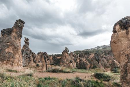 bizarre rock formations against cloudy sky in cappadocia, turkey