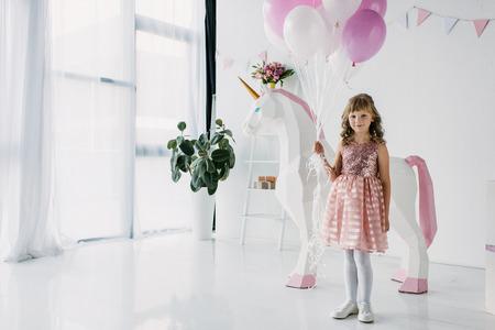 Geburtstagskind, das Bündel Luftballons hält und mit dekorativem Einhorn steht