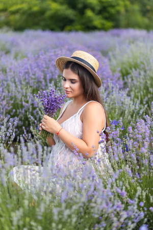 beautiful pregnant woman in white dress sniffing lavender flowers in field