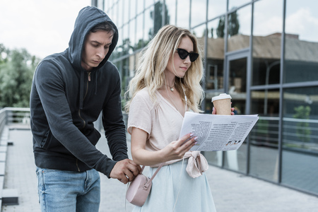 woman with coffee to go reading newspaper while robber pickpocketing from her bag