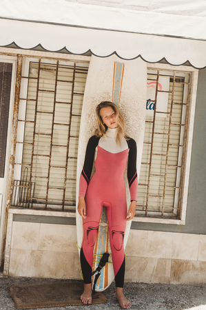 young woman in wetsuit with surfing board standing against building wall in Portugal Stock Photo