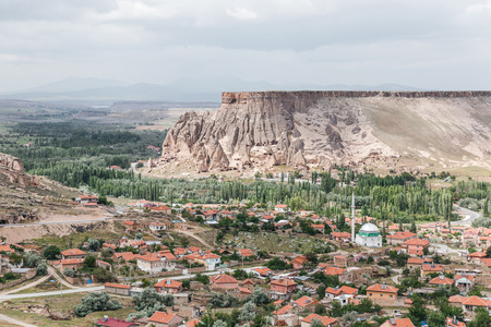majestic landscape with bizarre rock formations and buildings in cappadocia, turkey