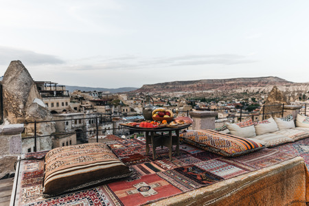 round table, traditional pillows and turkish carpet on terrace and beautiful view of traditional architecture and rocks in cappadocia, turkey