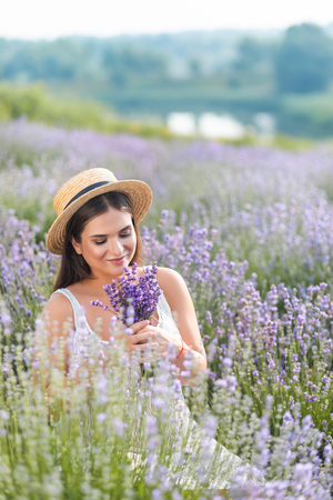 Smiling beautiful woman in white dress sniffing lavender flowers in field