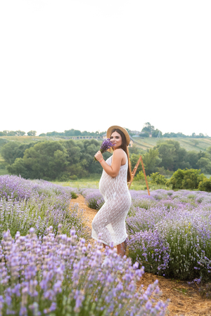 beautiful smiling pregnant woman in white dress sniffing lavender flowers in field Imagens