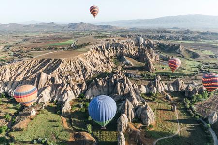 CAPPADOCIA, TURKEY - 09 MAY, 2018: hot air balloons flying above famous rock formations in cappadocia, turkey