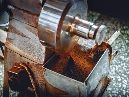 close-up shot of coffee mill pouring coffee powder into container