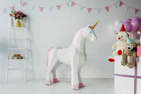 decorative unicorn, teddy bears in cones and air balloons in decorated for birthday room