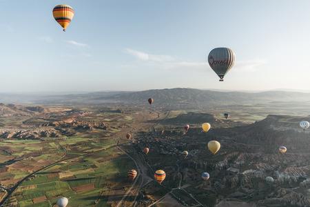 CAPPADOCIA, TURKEY - 09 MAY, 2018: colorful hot air balloons flying above majestic landscape in cappadocia, turkey Imagens
