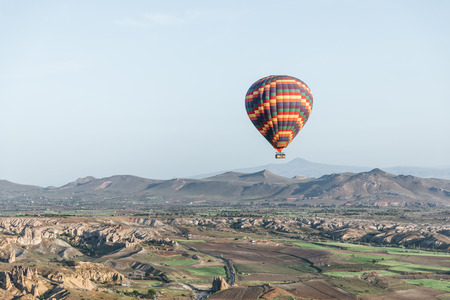 CAPPADOCIA, TURKEY - 09 MAY, 2018: colorful hot air balloon flying above goreme national park, cappadocia, turkey Stock Photo