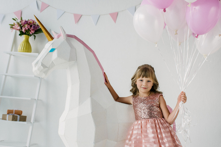 adorable little kid holding bunch of air balloons and standing with decorative unicorn