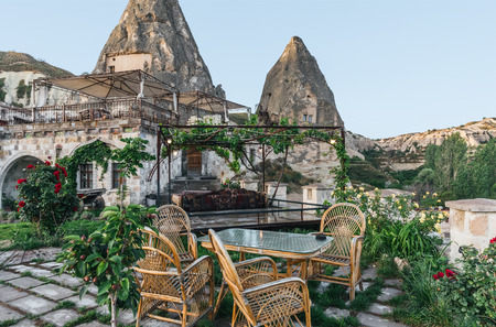 table and chairs on terrace and majestic view at bizarre rock formations in cappadocia, turkey Imagens